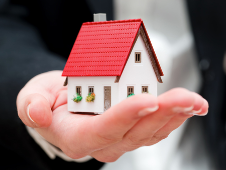 A real estate agent holding a small new house in her hands. Conceptual photo