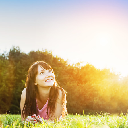 hope: Young beautiful woman smiling and lying on the grass at summer sunset looking at the sky  Natural happiness, fun and harmony