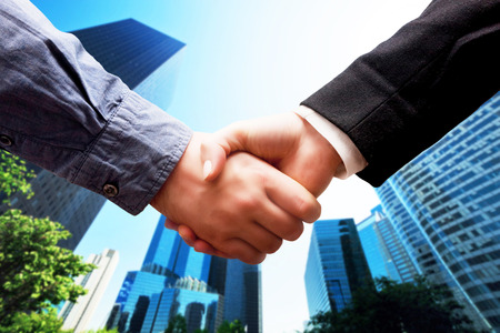 Business handshake on modern skyscrapers background. Deal, success, contract, cooperation concepts  photo