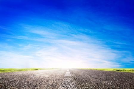 Lange lege asfaltweg, snelweg richting zon. Reizen, vervoersconcepten