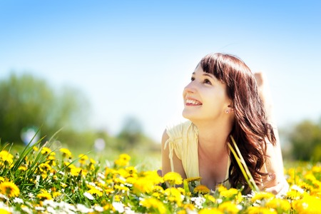 Young beautiful woman lying on grass full of spring flowers, looking happy at the sunny blue sky  Happiness, harmony, wellness, relaxation concepts
