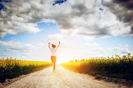 Happy young woman running and jumping for joy towards sun on the spring field Concepts of success, happiness, harmony, health, ecology