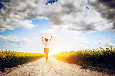 human health: Mujer joven feliz corriendo y saltando de alegr�a hacia el sol en los conceptos de campo de primavera de �xito, la felicidad, la armon�a, la salud, la ecolog�a