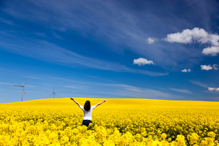 raised hands: Happy young woman with hands raised on spring field of yellow flowers, rape  Blue sunny sky  Concepts of success, happiness, harmony, health, ecology Stock Photo