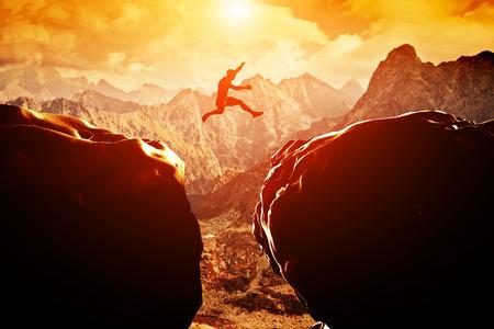 Hombre que salta sobre precipicio entre dos montañas rocosas en la puesta del sol Libertad, riesgo, desafío, éxito
