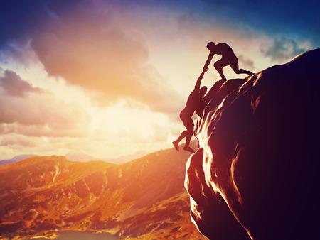 bergbeklimmen: Wandelaars klimmen op rots, berg bij zonsondergang, een van hen geven hand en helpen om hulp te klimmen, ondersteuning, hulp in een gevaarlijke situatie Stockfoto