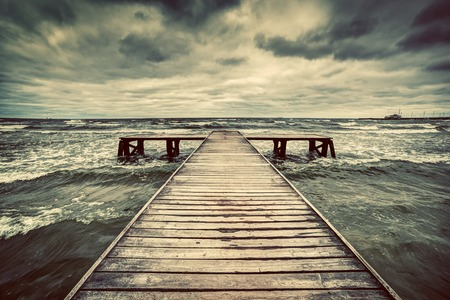 pier: Old wooden jetty, pier, during storm on the sea. Dramatic sky with dark, heavy clouds. Vintage