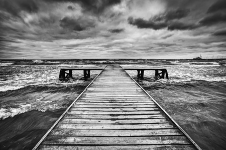 old pier: Old wooden jetty, pier, during storm on the sea. Dramatic sky with dark, heavy clouds. Black and white