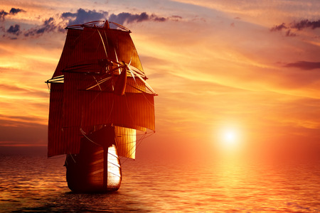 historical battle: Ancient pirate ship sailing on the ocean at sunset. In full sail. Stock Photo