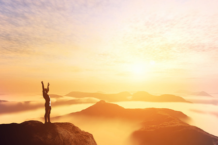 Hombre feliz con las manos en alto en la cima del mundo, por encima de las nubes y las montañas. El éxito, ganador, futuro brillante Foto de archivo