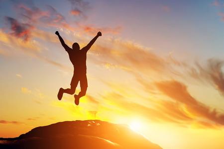 Uomo felice che salta di gioia sul picco della montagna, scogliera al tramonto. Successo, vincitore, felicità