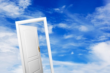 Open door on blue sunny sky with fluffy clouds. Concepts like new life, success, future perspective, hope, religion.