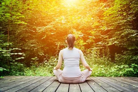 persona respirando: Mujer joven meditando en un bosque sentado en un suelo de madera. Zen, la meditación, la relajación, la salud espiritual, respiración sana