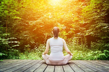 Young woman meditating in a forest sitting on a wooden floor. Zen, meditation, relax, spiritual health, healthy breathing Stock Photo