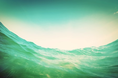 Dynamic water wave in the ocean. View from the waterline. Underwater and sunny sky. Vintage photo