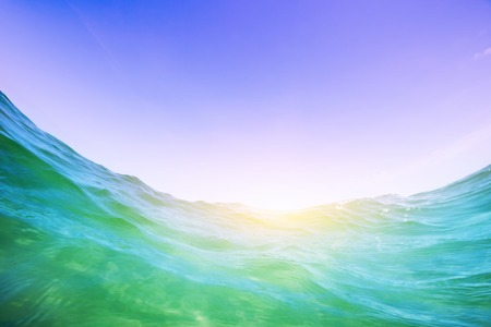 Dynamic water wave in the ocean. View from the waterline. Underwater and blue sunny sky. photo