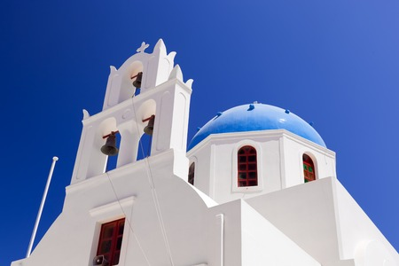 ia: A white church with blue dome in Oia or Ia on Santorini island, Greece. Traditional architecture and famous tourist attraction