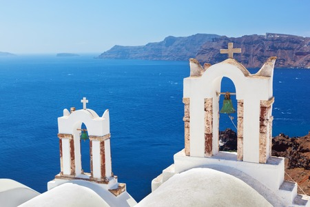 thera: Oia town on Santorini island, Greece. Traditional bells and crosses over the Caldera, Aegean sea