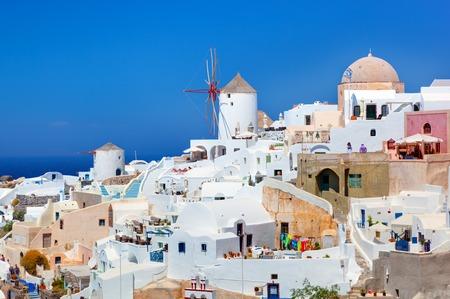 aegean sea: Oia town on Santorini island, Greece. Famous windmills on cliff over the Caldera, Aegean sea. Stock Photo