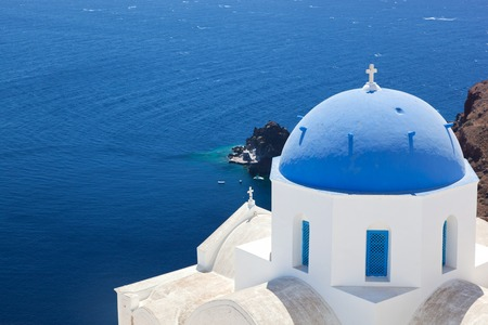 thera: Oia town on Santorini island, Greece. Traditional and famous church with blue dome over the Caldera, Aegean sea Stock Photo