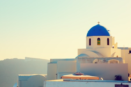 thera: Oia town on Santorini island, Greece at sunset. Traditional and famous church with blue domes over the Caldera, Aegean sea