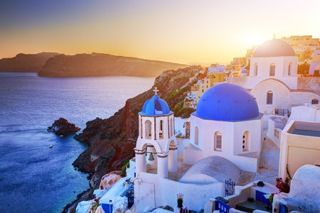 thera: Oia town on Santorini island, Greece at sunset. Traditional and famous churches with blue domes over the Caldera, Aegean sea