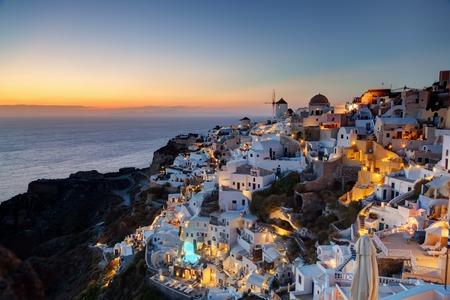 aegean sea: Oia town on Santorini island, Greece at sunset. Traditional and famous windmills on cliff over the Caldera, Aegean sea.