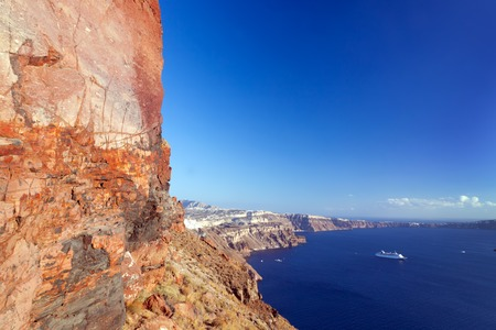 thera: Cliff and volcanic rocks of Santorini island, Greece. View on Caldera and Aegean sea, sunny day, blue sky.