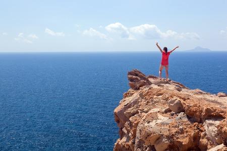 ganador: Mujer feliz en la roca con las manos en alto. Conceptos ganador, �xito,, turismo activo. La isla de Santorini, Grecia. Ganador, �xito, conceptos de turismo activo