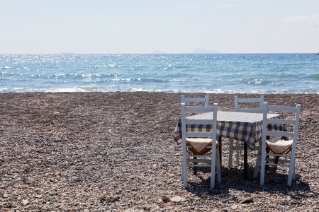 Table with chairs on the beach. Tavern, restaurant in Greece, Santorini. photo