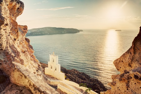 caldera: Cliff, volcanic rocks and a traditional chapel on Santorini island, Greece. View on Caldera and Aegean sea at sunset Stock Photo