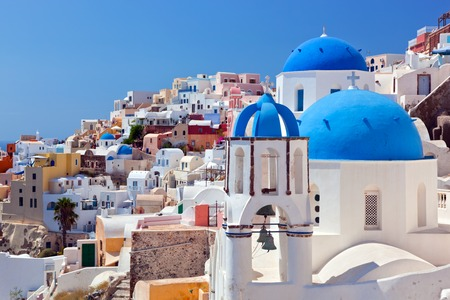 thera: Oia town on Santorini island, Greece. Traditional and famous houses and churches with blue domes over the Caldera, Aegean sea Stock Photo