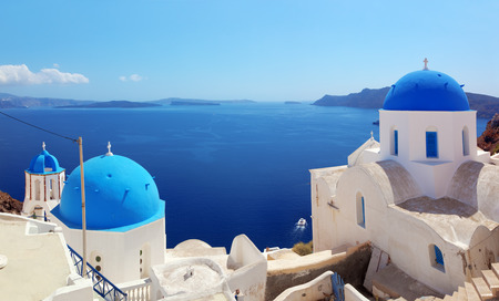 caldera: Oia town on Santorini island, Greece. Traditional and famous houses and churches with blue domes over the Caldera, Aegean sea. Panorama