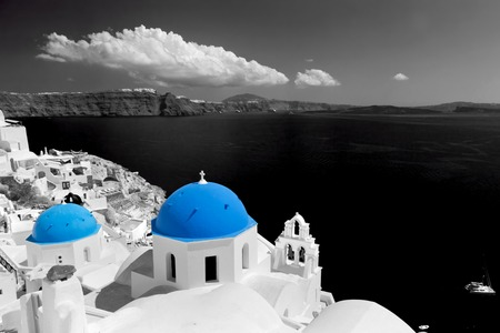 Oia town on Santorini island, Greece. Black and white styled with blue dome of traditional church over the Caldera, Aegean sea photo