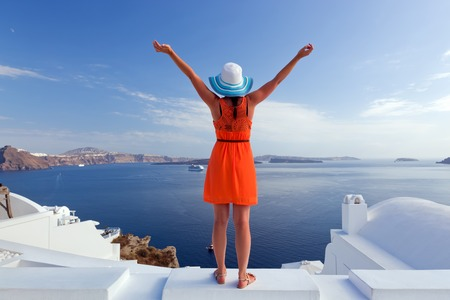 Happy woman in sun hat enjoying her holidays on Santorini island, Greece. View on Caldera and Aegean sea from Oia. Active, travel, tourist concepts photo