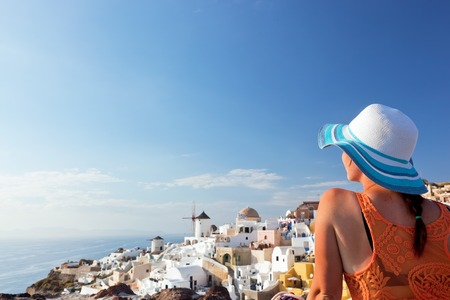 Happy woman in sun hat enjoying her holidays on Santorini island, Greece. View on Caldera and Aegean sea from Oia. Travel, tourist concepts