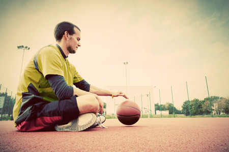 Young man on basketball court. Sitting and dribbling with ball. Streetball, training, activity. Real and authentic, vintage mood. photo