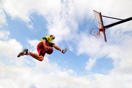pelota de basquet: Hombre joven saltando y haciendo una fantástica clavada jugando streetball, el baloncesto. Urban auténtico.