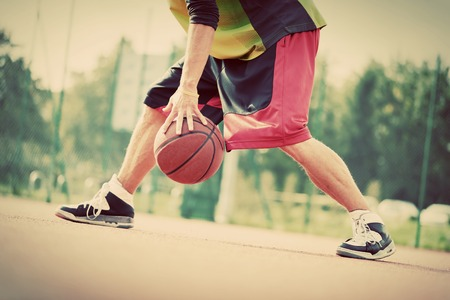 players: Young man on basketball court dribbling with ball. Streetball, training, activity. Real and authentic, vintage mood.