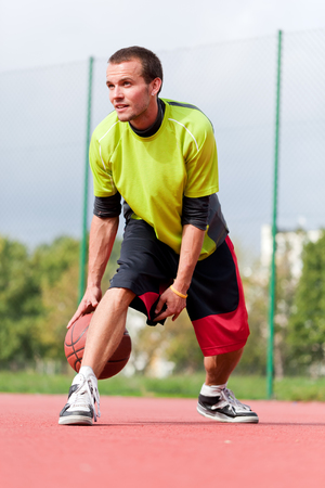 dribbling: Young man on basketball court dribbling with ball. Streetball, training, activity. Real and authentic