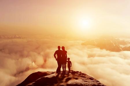 mujer mirando el horizonte: Familia de tres de pie juntos en la montaña y mirando el horizonte nubes al atardecer. Los padres y los niños, conceptuales.