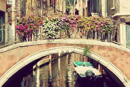 Venice, Italy. A bridge with flowers buquet over a narrow canal among old Venetian architecture. Vintage photo
