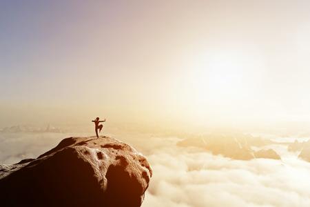 Asiatischer Mann, Kämpfer übt Kampfkunst im Hochgebirge über Wolken bei Sonnenuntergang. Kung Fu und Karate Pose. Auch Konzepte von Disziplin, Konzentration, Meditation etc. Einzigartig