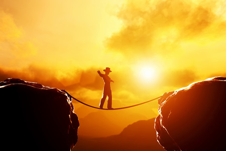 risk taking: Man in hat walking and balancing on rope over precipice in mountains at sunset. Concept of business, risk taking, challenge, concentration. Stock Photo