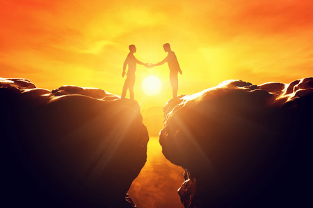 2 way: Two men shake hands over precipice between two rocky mountains at sunset. Business, deal, handshake, connection concepts