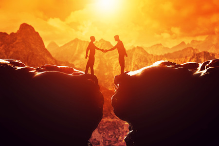 Two men shake hands over precipice between two rocky mountains at sunset. Business, deal, handshake, connection concepts