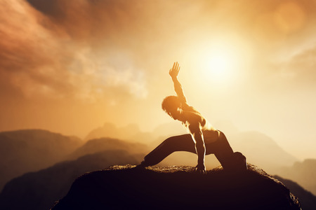 Asian man, fighter practices martial arts in high mountains at sunset. Kung fu and karate pose. Also concepts of discipline, concentration, meditaion etc. Unique