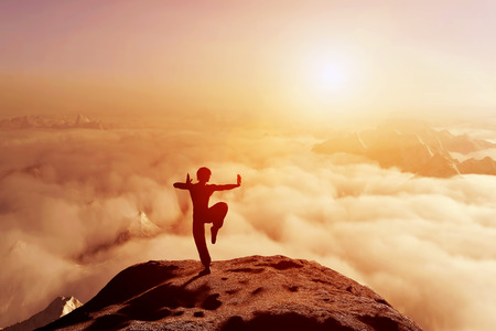 Asian man, fighter practices martial arts in high mountains above clouds at sunset. Kung fu and karate pose