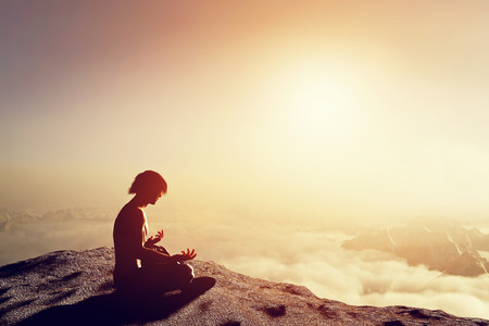 spiritual: Asian man meditates in yoga position in high mountains above clouds at sunset. Unique concept of meditation, spirituality, balance, harmony in life.