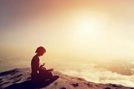 Aziatische man mediteert in yoga-positie in de hoge bergen boven de wolken bij zonsondergang. Uniek concept van meditatie, spiritualiteit, balans, harmonie in het leven. Stockfoto